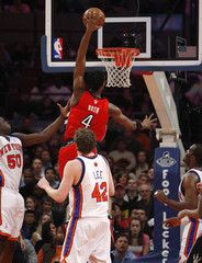 Toronto Raptors Bosh slam dunks past New York Knicks Randolph and Lee during the first half of the NBA basketball game in New York