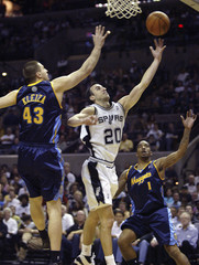 San Antonio Spurs guard Manu Ginobili goes up against Denver Nuggets forward Linas Kleiza and J.R. Smith in Texas