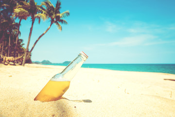Beer bottle on a sandy beach with palm tree. vintage color tone effect