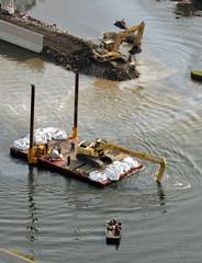 Workers repair the broken 17th Street levee in New Orleans.
