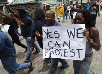 """Trinidadians walk with placards to demonstrate for more social action outside the """"People's Summit"""", which is being held at the same time as the 5th Summit of the Americas in Port of Spain"""