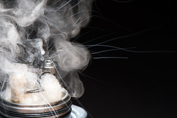 vaping with a wet cotton driptip on a black background for vaping, with a thick vapor and spray