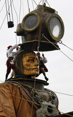 Crew members remove the helmet of a giant diver figure during a street theatre in Berlin