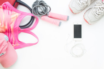 Overhead view of cellphone with sport bra, gap and jump rope in pink color collection on white background, Workout and Healthy concept, Top view