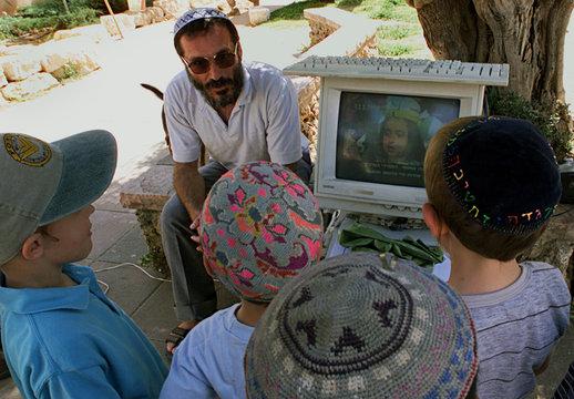 Jewish settler children gather around a computer screen showing Palestinian propaganda against Israe..