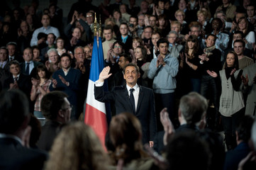 France's President Sarkozy waves to the public in an assembly hall in Saint Quentin