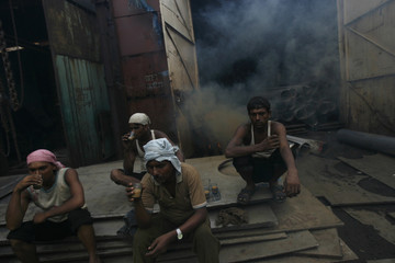 Workers drink tea during a refreshment break at a steel workshop in Mumbai