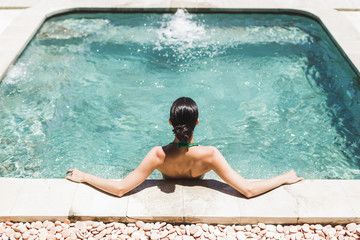 Woman in green swimsuit relaxing in outdoor jacuzzi with clean transparent turquoise water. Organic...