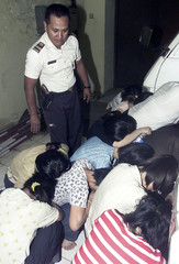 CHINESE NATIONALS HUDDLE IN JAKARTA AFTER THEIR ARREST FOR OVERSTAYING.