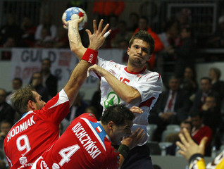 Norway's Kjelling attempts to score next to Poland's Siodmiak and Kuchczynski during their Men's World Handball Championship main round group II match in Zadar