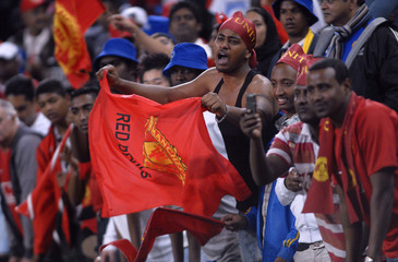 South African Manchester United supporters cheer during their team's Vodacom challenge soccer match against Orlando Pirates in the coastal city of Durban