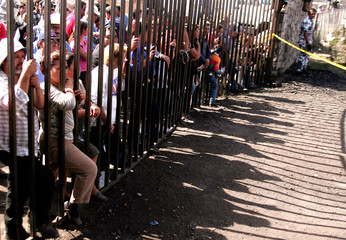 Relatives and friends stand behind gate of mine complex near San Juan de Sabinas in northern Mexico