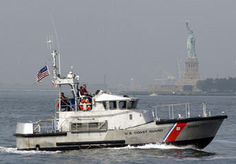 COAST GUARD BOAT PASSES STATUE OF LIBERTY.