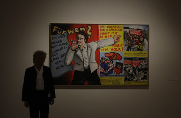 A security guide stands next to the painting Fuer wen? by Immendorff in Berlin