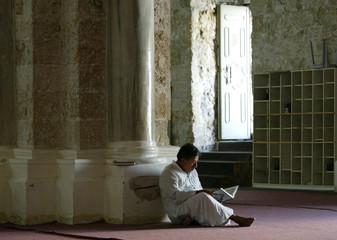 A PALESTINIAN MAN READS MOSLEM HOLY BOOK KORAN INSIDE AL-OMARE MOSQUEIN GAZA.