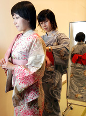 A Japanese woman in tradional yukata has a kimono fitter fix her obi belt in Tokyo.