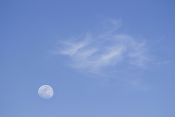 Moon and soft clouds in evening sky