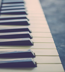 Keys of old piano. Side view. Vintage toning. Selective focus. Vertical photo
