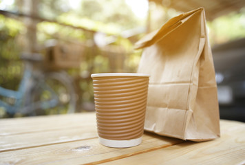cup coffee and bread in paper bag.