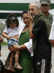 Italian Red Cross official Vagni wipes his eye as he is welcomed by his wife and their daughter upon his arrival at Villamor air base in Manila