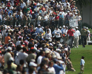 Phil Mickelson and Tiger Woods walk off the 1st hole of the Ford championship in Miami, Florida.