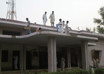Pakistani security officials survey the site of the suicide blast in the town of Bhakkar