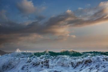 Sea wave crushing against sunset sky