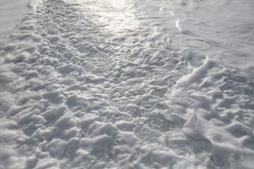 Sea foam pattern. White track after shorebreak wave crushed against beach sand