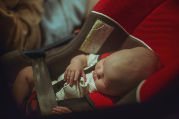 Baby sleeping on baby seat in a car at night
