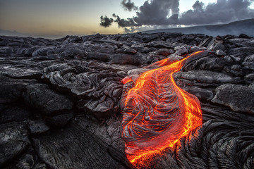 Red Orange vibrant Molten Lava flowing onto grey lavafield and glossy rocky land near hawaiian volcano with vog on background Fototapete