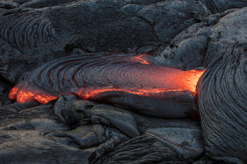 Molten magma red hot lava flowing on cold lavafiled in grey colored texture of volcanic background