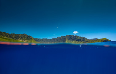 Mountain valley in ocean blue water. Tropical landscape splitted by water line.