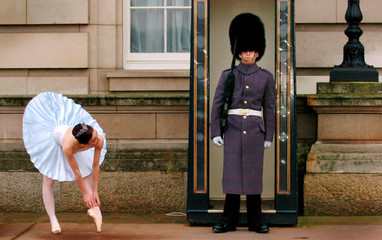 Clarke who plays Sugar Plum Fairy in The Nutcracker adjusts ballet shoes outside Buckingham Palace in London.