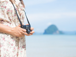 woman holding camera and walk on the beach seaside