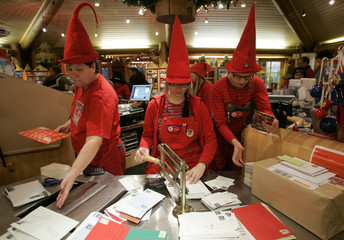People dressed as elves post mark letters with the stamp from Santa Claus' Post Office on the Arctic Circle near Rovaniemi