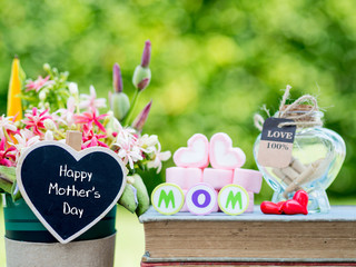 mother's day concept. MOM alphabet with marshmallow in the shape of heart and flower on background