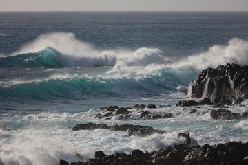 Black rocks in Pacific ocean shore with blue beautiful splashing storming waves