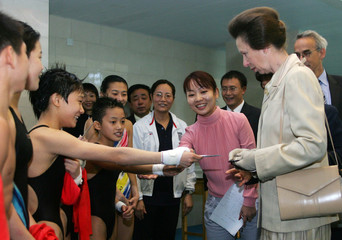 A young Chinese diver shows his identification card to Princess Anne of Britain during a visit in Beijing.