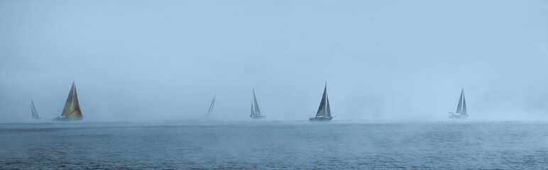 Sailing yachts floating in the foggy sea