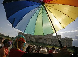 A member of Romania's gay community holds a rainbow umbrella in front of Parliament Palace during Gay Fest Parade in Bucharest