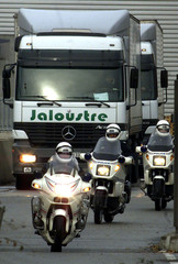 French motorcycle police escort trucks carrying euro coins as they leave the national mint in Pessac..