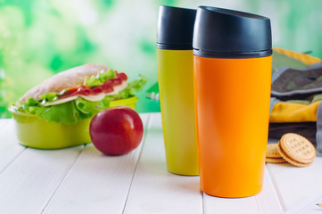 Color thermos mugs near lunch box and backpack on table