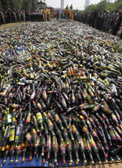 Officials destroy bottles of alcohol confiscated from street shops in Jakarta