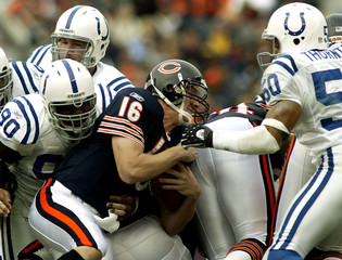 Colts Reagor tackles Bears Krenzel for a loss while Colts Thornton closes in.