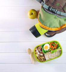 Top view of lunch box and backpack on light wooden background