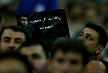 HIZBOLLAH SUPPORTERS CARRY POSTERS OF REBEL IRAQI SHI'ITE MUSLIM CLERIC MOQTADA AL-SADR AT A RALLY ...