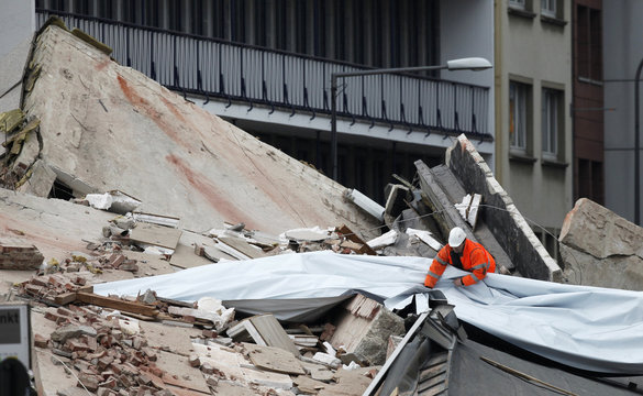 A member of the emergency services places a plastic sheet on top of the rubble of the collapsed building of the town archive in the German city of Cologne