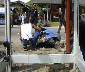 Police officials examine a trash bin after a bomb placed inside the bin exploded in Pattani Province