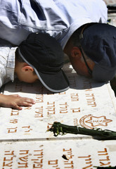 Israeli man and his son kiss tombstone at military cemetery on Mount of Olives in Jerusalem
