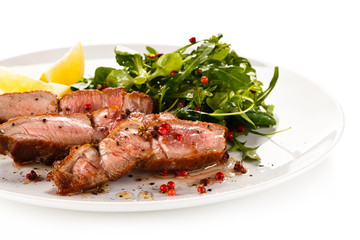 Grilled steak - fillet mignon on white plate with green salad